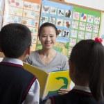 Teacher reading to her elementary school — Stock Photo