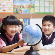 Schoolchildren looking at a globe in the classroom — Stock Photo #36654395
