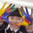 Schoolgirl finger painting, close up on hands — Stock Photo #36654491