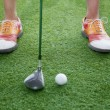 Feet and golf club getting ready to hit a golf ball — Stock Photo #36654731