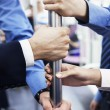 Business people's hands holding the pole on the subway — Stock Photo