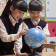 Schoolgirls looking at a globe in the classroom — Stock Photo