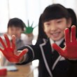 School children showing their hands covered in paint — Stock Photo