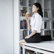 Businesswoman holding a coffee and sitting on a table — Stock Photo #36655357