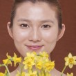 Woman behind a bunch of daffodils — Stock Photo #36655823