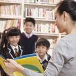 Teacher reading to her elementary school students — Stock Photo #36656387