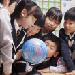 Schoolchildren looking at a globe in the classroom — Stock Photo