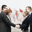 Stock Photo: Business people meeting and shaking hands outdoors