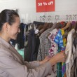 Woman going through clearance clothes at fashion store — Stock Photo #36657801