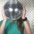 Woman holding a disco ball in front of her face — Stock Photo