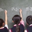 Three school children doing math equations — Stock Photo #36658443