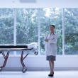 Stock Photo: Doctor standing next to stretcher
