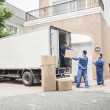Couple watching movers move boxes from the moving van — Stock Photo #36659147