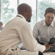Doctor and patient discussing medical record — Stock Photo #36659297