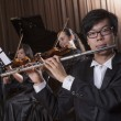 Stock Photo: Flautist holding and playing flute