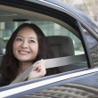 Постер, плакат: Woman in back seat of car fastening seat belt
