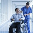 Nurse pushing patient in a wheelchair — Stock Photo