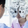 Постер, плакат: Optometrist doing an eye exam on young woman