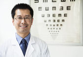 Optometrist with an eye chart in the background — Stock Photo