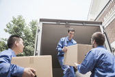 Movers unloading a moving van — Stock Photo