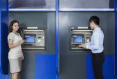 People standing and withdrawing money from an ATM — Stock Photo