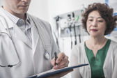 Doctor writing on medical chart with patient — Stock Photo