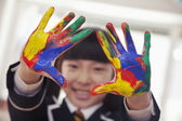Schoolgirl finger painting, close up on hands — Stock Photo