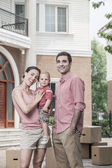 Smiling family in front of their new home — Foto Stock