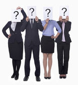 Business people holding up paper with question mark — Stock Photo