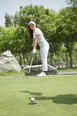 Woman hitting the ball on the golf course — Stock Photo