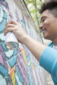 Man spray painting on a wall outside — Stock Photo