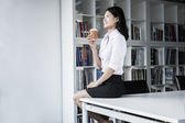 Businesswoman holding a coffee and sitting on a table — Stock Photo
