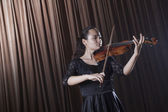 Violinist standing and playing the violin — Stock Photo