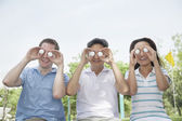 Friends in a row holding up golf balls in front of their eyes — Stock Photo