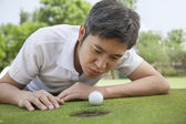 Man trying to blow the ball into the hole — Stock Photo