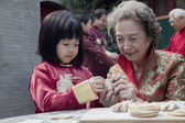 Grandmother and granddaughter making dumplings — Stock Photo