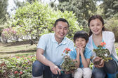 Family planting flowers — Stock Photo