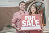 Couple holding a For Sale sign — Stock Photo