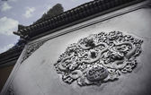 Ornate low relief sculpture of dragon on wall — Stock Photo