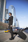 Businessman with luggage on the street hailing a cab — Stock Photo