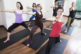People doing yoga during a yoga class — Stock Photo