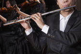 Flautist holding and playing the flute — Stock Photo