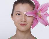 Frau mit einem großen rosa blume versteckt hinter dem ohr — Stockfoto