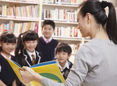 Teacher reading to her elementary school students — ストック写真