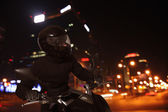 Young Man riding a motorcycle at night — Stock Photo
