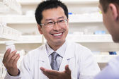 Pharmacist showing prescription medication to a customer — Stock Photo