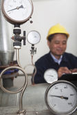 Gas gauges with worker in the background — Stock Photo