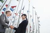 Businesswomen shaking hands outdoors — Stock Photo