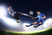 Two soccer players in mid air kicking the soccer ball — Stock Photo