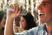 Man singing at karaoke, friends singing in the background — Stock fotografie